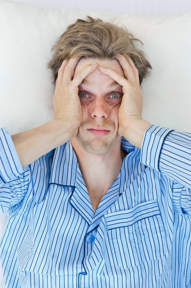 Man lies awake, frustrated from suffering from sleep apnea which is affecting his overall health.