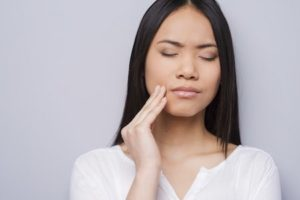 Woman feeling the side of her face because of tooth pain is looking for an emergency dentist appointment at River Valley Dental in Hadley MA.